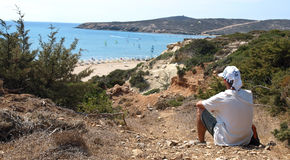 Prasonisi viewpoint. Cape Prasonisi - young man looking down at the beach in beautiful nature royalty free stock photos
