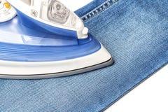 Prasowanie niebiescy dżinsy na białym baclground obraz stock