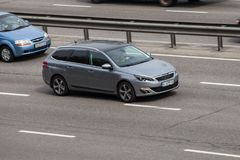 Prata luxuosa Peugeot do carro que apressa-se na estrada vazia Imagens de Stock