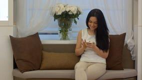 Prata och smsande meddelanden för attraktiv ung kvinna på mobiltelefonsammanträde på soffan Arkivfoton