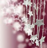 A prata Stars a festão no fundo cor-de-rosa do borrão Fotos de Stock