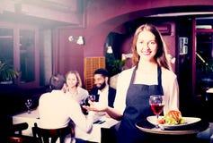 Prata vuxna människor och den gladlynta servitrins fotografering för bildbyråer