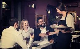 Prata vuxna människor och den gladlynta servitrins royaltyfria foton