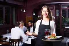 Prata vuxna människor och den gladlynta servitrins royaltyfri bild