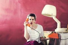 Pratar den ilskna hemmafrun för tappning på telefonen i hårsalong Royaltyfria Foton