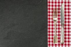 Pratas em uma placa da ardósia com uma toalha de mesa quadriculado vermelha Fotos de Stock Royalty Free