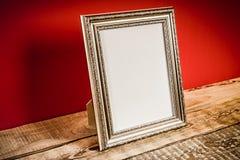Prateleira com quadro e a parede vermelha Fotos de Stock