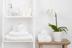 Prateleira com toalhas limpas, velas, vaso de flores na tabela de madeira do banheiro Foto de Stock