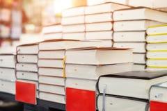 Prateleira da livraria com a pilha dos novos livros com a placa vazia vermelha Chegadas novas na livraria Apresentação do livro C foto de stock
