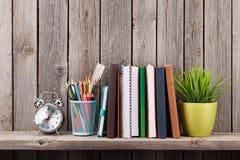 Prateleira de madeira com livros e fontes Fotos de Stock Royalty Free