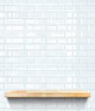 Prateleira de madeira vazia na parede cerâmica da telha branca, zombaria do molde acima de f imagem de stock
