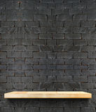Prateleira de madeira vazia na parede de tijolo preta, zombaria do molde acima para o disp imagens de stock