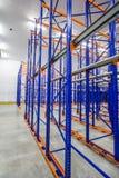 prateleiras azuis e alaranjadas do metal para armazenar bens em um grande complexo do armazém imagem de stock