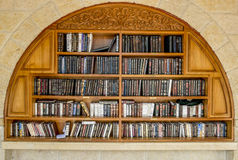 Prateleiras com os livros religiosos perto da parede lamentando no Jerusalém Fotos de Stock