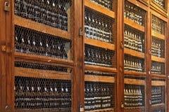 Prateleiras de madeira com os frascos do vinho Foto de Stock