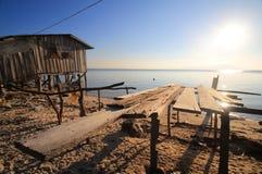 Prateleiras de madeira incompletas em uma praia ao lado de uma casa de madeira, enfrentando o mar e o sol de ajuste Imagem de Stock