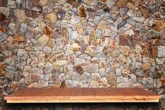 Prateleiras de madeira superiores vazias e fundo da parede de pedra fotos de stock royalty free