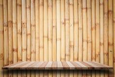 Prateleiras de madeira superiores vazias e fundo de bambu da parede Imagens de Stock