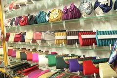 Prateleiras enchidas com os sacos de mão brilhantes das senhoras Imagem de Stock