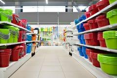 Prateleiras na loja com utensílios plásticos Cremalheira com bens variados Venda, comércio Imagens de Stock Royalty Free