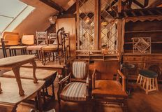 Prateleiras velhas e mobília de madeira na casa histórica com cadeiras e decoração do vintage imagens de stock royalty free