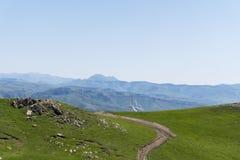 Prati e strada campestre, la cima del paesaggio della montagna fotografie stock