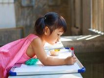 Pratica adorabile del bambino per la scrittura su vasto bianco prima di classe lear Immagine Stock