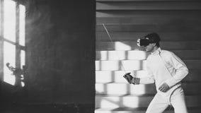 Pratica concentrata dell'uomo dello schermitore che recinta gli esercizi facendo uso della cuffia avricolare di VR e che prepara  Fotografie Stock Libere da Diritti