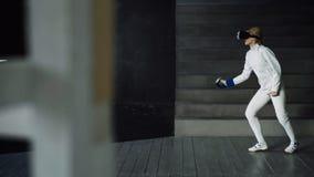 Pratica concentrata della donna dello schermitore che recinta gli esercizi facendo uso della cuffia avricolare di VR e che prepar Fotografia Stock Libera da Diritti