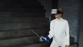 Pratica concentrata della donna dello schermitore che recinta gli esercizi facendo uso della cuffia avricolare di VR e che prepar Fotografie Stock Libere da Diritti