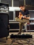 Pratica della chitarra nello studio Immagine Stock