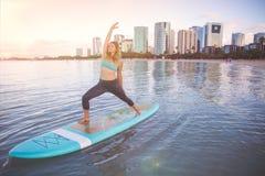 Pratica di yoga del SUP di alba nella posa del guerriero di Waikiki Immagine Stock