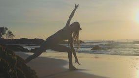 Pratica di yoga della siluetta al tramonto Donna di Yong che fa esercizio di yoga sulla spiaggia archivi video
