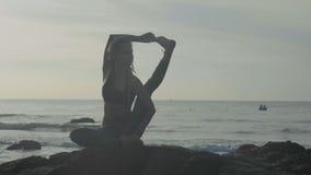 Pratica di yoga della siluetta al tramonto Donna di Yong che fa esercizio di yoga sulla spiaggia video d archivio