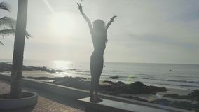 Pratica di yoga della siluetta al tramonto Donna di Yong che fa esercizio di yoga sulla spiaggia stock footage