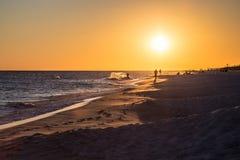 Praticando il surfing al tramonto Immagine Stock