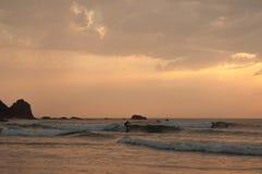 Praticando il surfing al tramonto in spiaggia di Algarve Castelejo, il Portogallo Fotografie Stock Libere da Diritti
