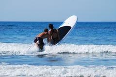 Praticando il surfing con i bambini Immagini Stock Libere da Diritti