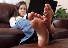 Praticando il surfing il Internet con i piedi in su Fotografie Stock Libere da Diritti