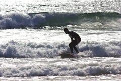Praticando il surfing l'oceano al tramonto Immagini Stock