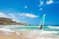 Praticando il surfing sulla costa di mare Fotografie Stock