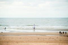 Praticando il surfing sulla spiaggia fotografia stock