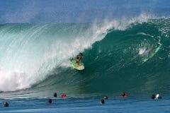Praticando il surfing un'onda alla conduttura immagine stock
