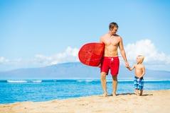 Praticare il surfing andante del figlio e del padre Immagini Stock