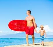Praticare il surfing andante del figlio e del padre Immagine Stock Libera da Diritti