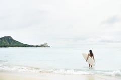Praticare il surfing andante della ragazza del surfista sulla spiaggia Hawai di Waikiki Fotografia Stock