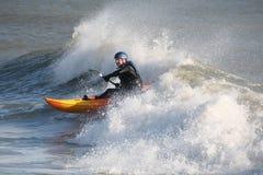 Praticare il surfing dell'onda del mare del kajak Immagini Stock