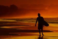 Praticare il surfing di tramonto Fotografia Stock Libera da Diritti