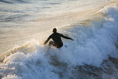 Praticare il surfing di tramonto Fotografie Stock