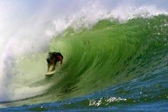 Praticare il surfing il tubo di un'onda fotografia stock